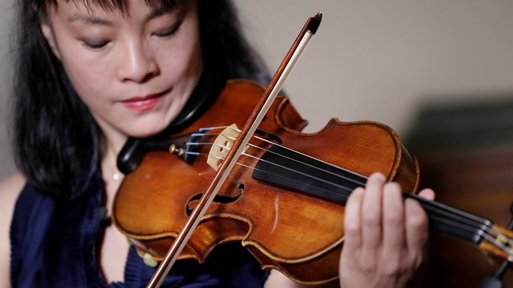 FILE - In this March 8, 2017, file photo, violinist Mira Wang plays the Ames Stradivarius violin in New York. After a meticulous restoration that took more than a year, the Stradivarius violin that was stolen from violinist Roman Totenberg is about to return to the stage. Wang, a former student of Totenberg's, will play the instrument at a private concert in New York on Monday, March 13, 2017.