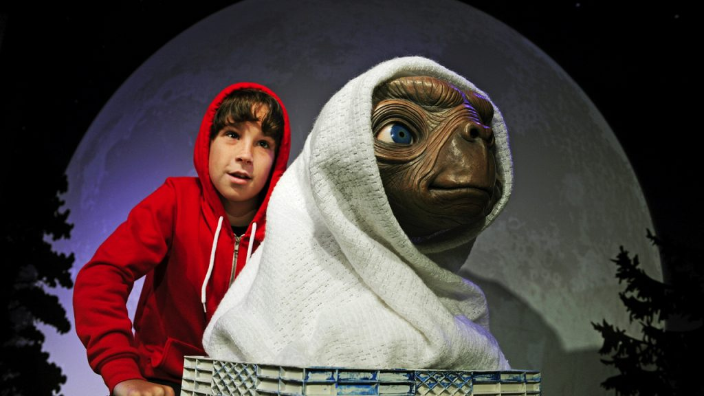 """AUSTRALIA-ENTERTAINMENT-WAXWORKS-CINEMA-ET Local Sydney BMX rider Lachlan Stewart re-enacts the iconic scene from the Steven Spielberg movie classic """"E.T. The Extra-Terrestrial"""" during an unveiling of the E.T. wax exhibit at Madame Tussauds in Sydney on October 22, 2012. In celebration of the Blu-ray release and the 30th anniversary of E.T. a global launch of the film's most iconic character re-enacting the classic moment in film has begun in Sydney, with Berlin, Amsterdam, London, Hollywood and Tokyo to follow. AFP PHOTO / Greg WOOD"""