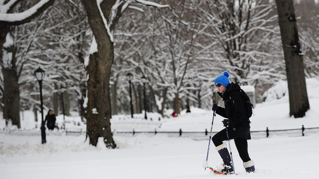 A woman walks with snowshoes after heavy snow falls in Central Park in New York, January 27, 2011. New York shut down two airports, public schools and most city services in the wake of a rare thunder-snow storm that paralyzed air and ground travel over a vast area from Washington to as far north as Boston. AFP PHOTO/Emmanuel Dunand (Photo credit should read EMMANUEL DUNAND/AFP via Getty Images)